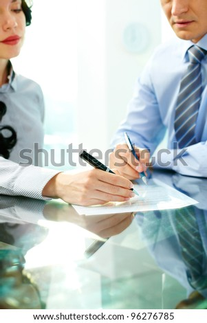 Two business partners signing an agreement - stock photo
