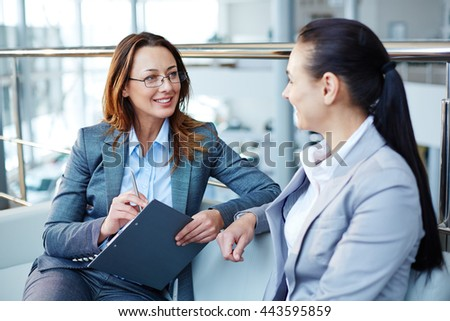 Two business partners sitting and communicating with each other - stock photo