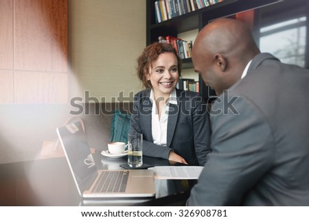 Two business partners sitting in cafe and discussing business plan. Businessman and businesswoman smiling during meeting in a coffee shop. - stock photo