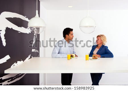 Two business partners talking during lunch in the office lunchroom