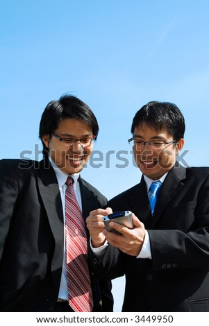 Two business partners working together looking at a PDA - stock photo