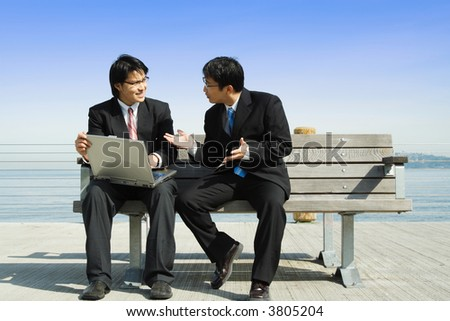 Two business partners working together on a laptop - stock photo
