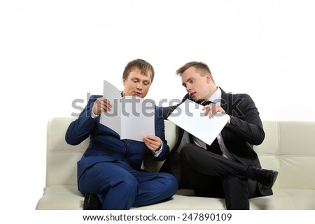 Two business people analyze current business situation and plans for the future. There may be knowledge-sharing context as well.  Copy space on the magazines or above is for your text.  - stock photo
