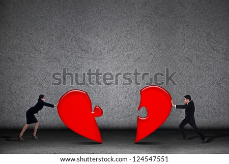 Two business people are putting love puzzle together on grey background - stock photo
