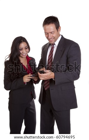 Two business people are standing next to each other texting.