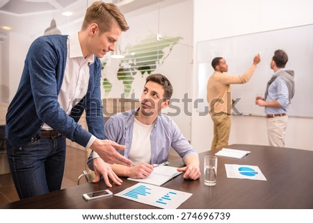 Two business people are talking sitting at the table on background of colleagues. - stock photo