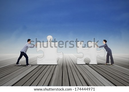 Two business people are working together to put two puzzles - stock photo