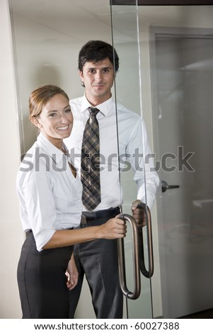 Two business people at door of office boardroom