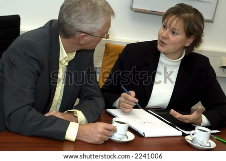 Two business people discussing. Focus is on the woman. - stock photo