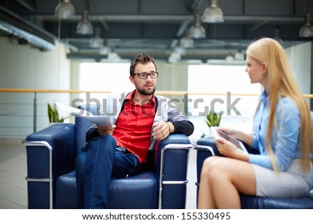Two business people discussing plans or ideas while sitting in office  - stock photo