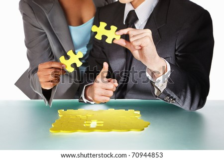 Two business people discussing the right last piece of the puzzle