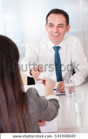 Two Business People Exchanging Card In Office - stock photo