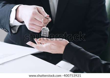 Two business people handing over the keys after a successful deal - stock photo