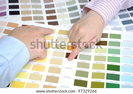 Two business people hands pointing to color samples - stock photo