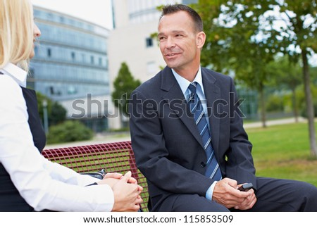 Two business people having a chat on a park bench - stock photo