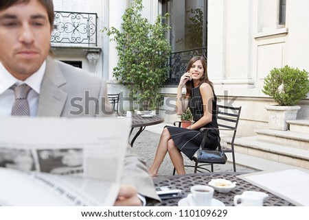 Two business people in a classic building's terrace reading the newspaper and talking on the cell phone. - stock photo