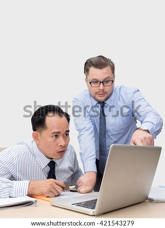 Two business people in bright shirts sitting at desk working in team together, discussing the problem, point finger on laptop, clipboard with papers, document, over gray background