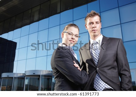 Two business people in suits against the business building - stock photo