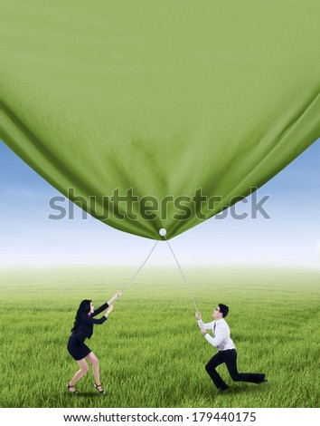 Two business people is pulling green banner on the meadow - stock photo