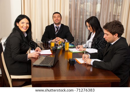Two business people laughing and other two business people being serious and writing at business meeting - stock photo