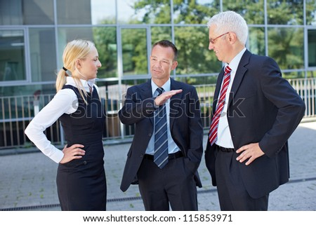 Two business people listening to the speech of a manager - stock photo
