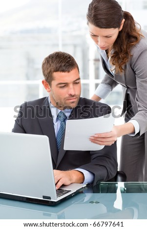 Two business people looking at a paper while working on the laptop in the office - stock photo