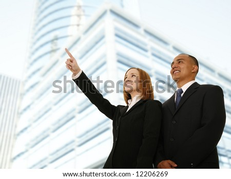 two business people, man and woman standing in front of business building. the woman pointing to somewhere. concept for business team or business plan - stock photo