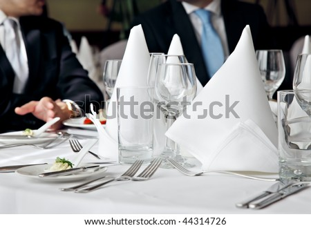 two business people no faces over a restaurant table - stock photo