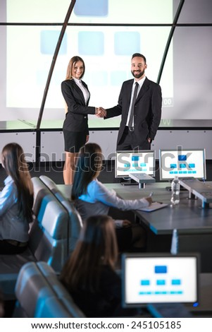 Two business people on the podium during presentation. People at the conference hall. Rear view. - stock photo