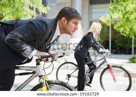 Two business people racing on the bicycle showing competition
