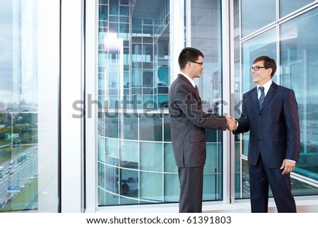 Two business people shake hands in the office - stock photo
