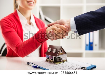 Two business people shaking hands as successful agreement in real estate agency office. Concept of housing purchase and insurance.  - stock photo