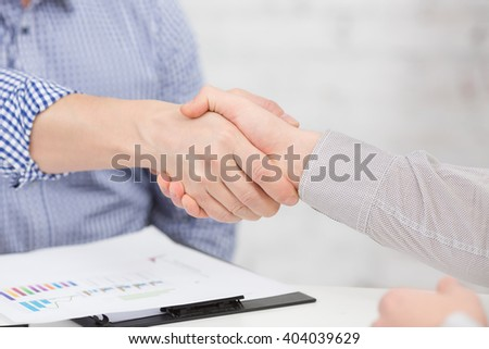 Two business people shaking hands indoors. Man and woman are business partners, who agreed to sign contract or agreement. - stock photo