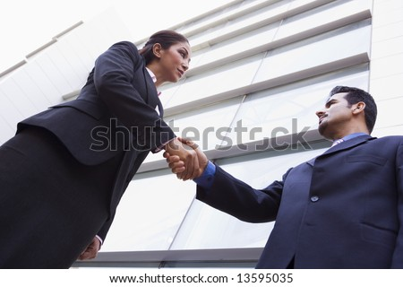 Two business people shaking hands outside modern office - stock photo