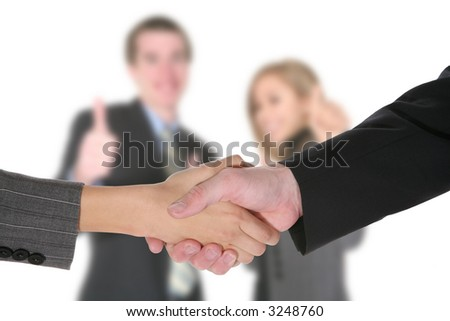 Two business people shaking hands with coworkers in the background