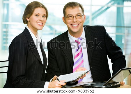 Two business people sitting at the table with a laptop on it in the office