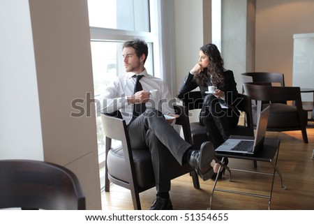 Two business people sitting on armchairs during coffee pause