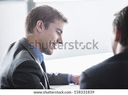 Two business people smiling and looking down at business meeting - stock photo