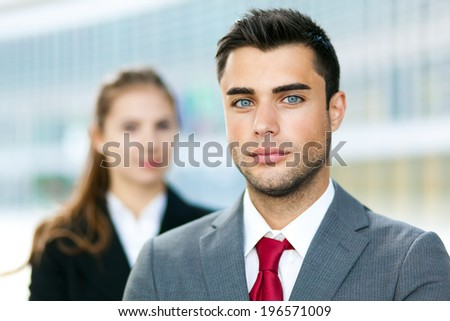 Two business people smiling in an urban setting  - stock photo