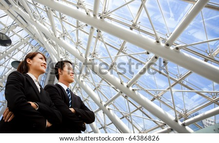 two business people stand in modern office - stock photo
