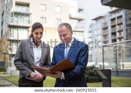 Two business people standing and discussingin front of the office - stock photo