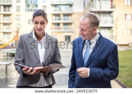 Two business people standing and discussingin front of the office