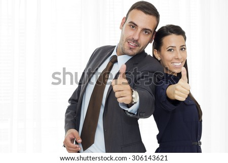Two business people standing  with thumb up happily looking at camera.  - stock photo
