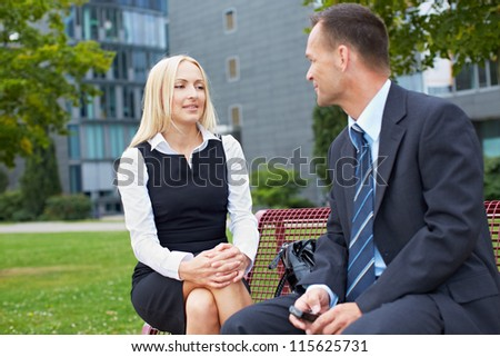 Two business people talking outside on a park bench - stock photo