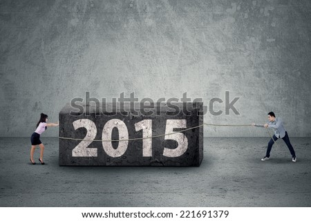 Two business people try to move a boulder as an obstacle in 2015 - stock photo