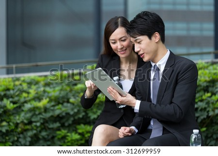 Two business people using the tablet for report - stock photo