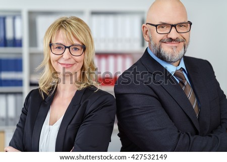 Two business people wearing glasses and suits stand with arms crossed and shoulder to shoulder near shelf - stock photo