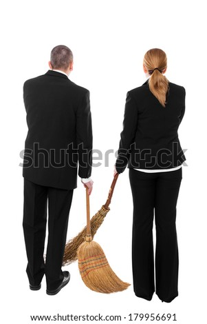 two business people with brooms making a inappropriate working - stock photo