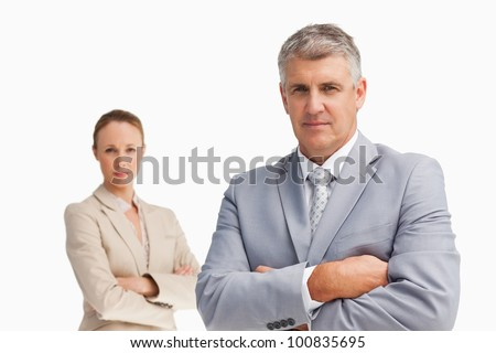 Two business people with folded arms against white background