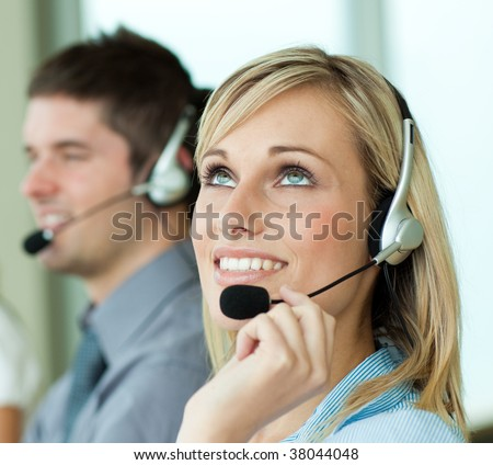 Two business people with headsets in an office - stock photo